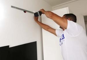 Pose des éléments hauts à l'aide de réglettes servant à accrocher les meubles et à les ajuster avec précision.