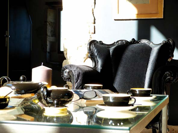 Le salon en velours noir de type baroque a été chiné sur le Bon Coin. Le service à thé des années 50 (Villeroy & Bosch) a été chiné sur un vide-grenier.