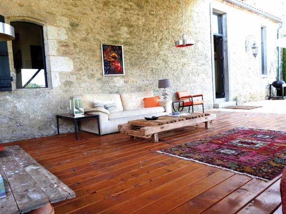 """Sur la terrasse couverte, les luminaires en inox brossés ont été achetés à la Clinique du Luminaire à  Le canapé en velours beige """"années 80"""" a été chiné (Le Grenier d'Antan). Le fauteuil orange """"années 70"""" provient d'un vide-grenier, comme la tapisserie accrochée au mur. La table basse a été fabriquée avec un appareil à presser les feuilles de tabac trouvé dans la maison. Tapis année 30 (Le Bon Coin). A gauche, la table basse a été réalisée avec une vieille porte trouvée sur place et de quatre pots de fleurs en terre. Sol en cèdre (Charpente Conord)."""