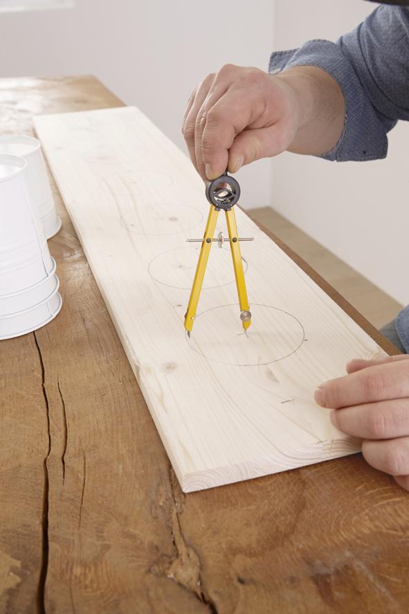 ETAPE 1 : Commencer par scier la planche à la longueur désirée avec la scie multifonctions sans fil PST 10,8 LI Bosch. Dans notre exemple, nous avons prévu 1 m de longueur pour six pots à herbes. Puis à l'aide d'un cercle, tracer les contours des trous dans lesquels les pots seront ensuite placés. Le diamètre doit être d'environ 1 cm inférieur à celui du bord supérieur des pots pour que ces derniers ne puissent pas glisser au travers des trous.