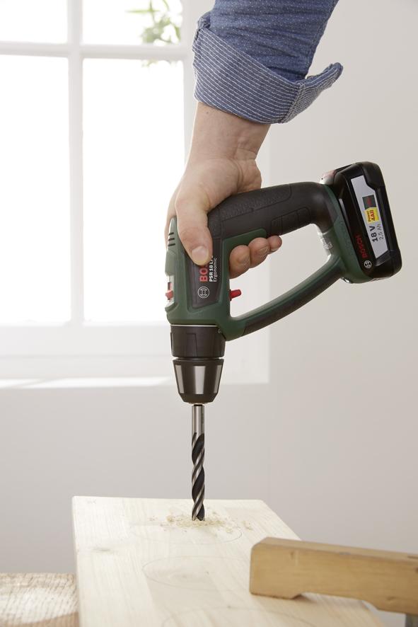 ETAPE 2 : Percer les quatre trous pour les câbles métalliques aux encoignures de la planche. Pour ce faire, utiliser la perceuse-visseuse sans fil PSR 18 LI-2 Ergonomic Bosch avec une mèche à bois (dans notre exemple, nous utilisons une mèche de 2,5 mm adaptée à l'épaisseur du câble métallique). La perceuse- visseuse sans fil permet également de préparer le découpage des trous pour les pots : pour ce faire, simplement percer un trou sur le bord interne du cercle tracé à l'aide d'une mèche à bois assez grosse (18 mm).