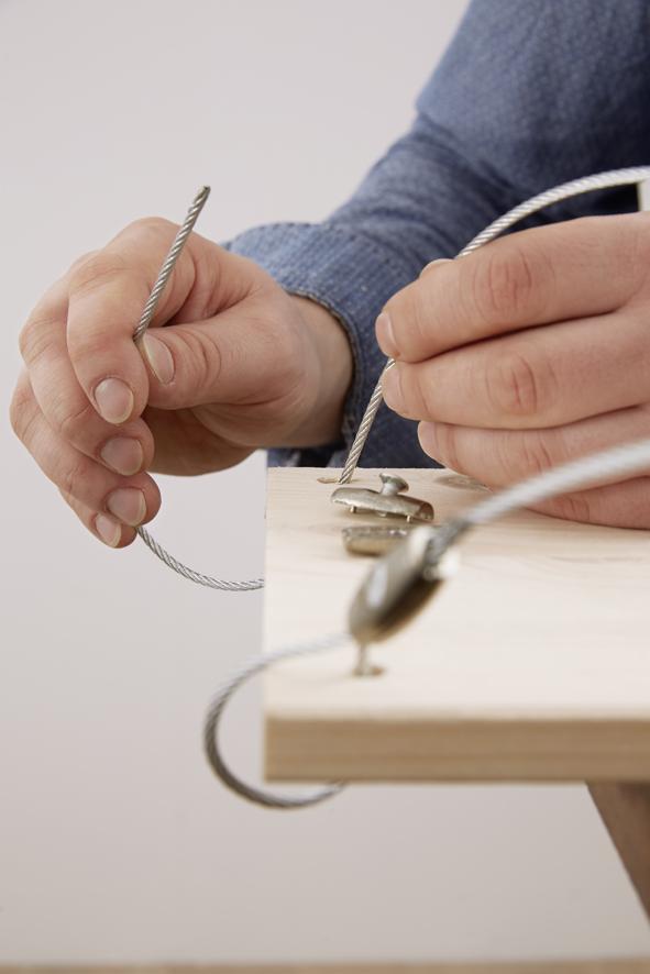 ETAPE 5 : Avant l'accrochage, percer quatre trous pour les crochets de plafond à l'aide de la perceuse-visseuse sans fil et d'une mèche adaptée à la nature du plafond. Les trous doivent être espacés comme les trous préalablement percés aux encoignures de la planche. Enfoncer les chevilles et visser fermement les crochets de plafond. Couper ensuite le câble métallique à la longueur souhaitée. Enfiler les extrémités inférieures dans la planche par les trous et fixer avec quatre serre-câbles pour que l'étagère soit fermement suspendue.Enfiler également le câble dans les crochets de plafond et fixer avec les quatre serre-câbles restants. Enfin planter du basilic, du romarin, de la menthe ou d'autres herbes dans les pots pour les avoir toujours à proximité !