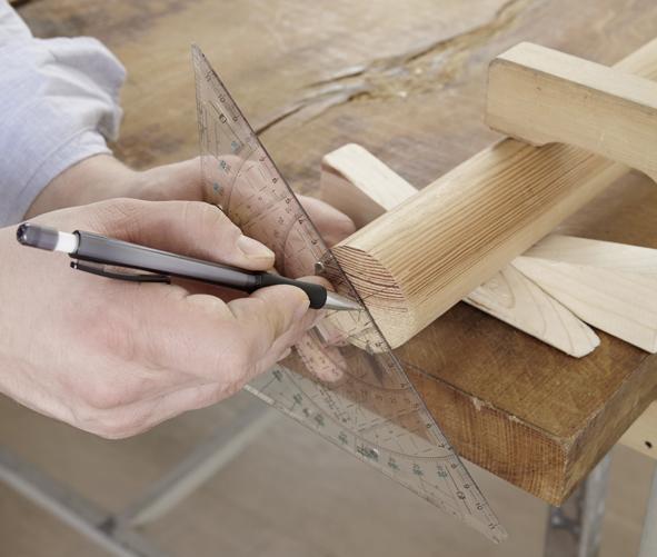 ÉTAPE 1 Pour que les baguettes de batterie deviennent des supports à chaussures, il faut des trous précis. Il est donc recommandé de tracer des lignes de repère. Pour cela, fixer d'abord le bâton de bois à la table de travail. Marquer ensuite le centre des arêtes de coupe extérieures du bâton. Les deux centres sont reliés entre eux par une ligne droite qui passe au milieu du bâton. Cette ligne de repère partage fictivement en deux moitiés strictement égales. Fixer maintenant le bâton sur la table de travail de sorte que la ligne médiane soit précisément orientée vers le haut. Tracer ensuite deux autres lignes de repère le long desquelles les baguettes de batteries seront fixées. Pour cela, tracer deux autres lignes parallèles en partant de la ligne médiane, situées 5 cm à droite et à gauche de la ligne médiane. Sur la ligne de repère de gauche, poser une marque tous les 12 cm pour les huit trous qui seront faits, en commençant à une distance de 5 cm de l'arête de coupe extérieure droite du bois rond. Sur la ligne de repère de droite, marquer les huit autres trous également avec un écartement de 12 cm. Commencer cette fois à une distance de 5 cm de l'arête de coupe extérieure gauche du bâton, afin que les trous du côté droit se trouvent à 6 cm des trous du côté gauche. Le dernier trou des deux lignes de repère se trouve à une distance de 11 cm des arêtes de coupe. De cette manière, huit baguettes sont ensuite fixées de chaque côté de la ligne médiane.