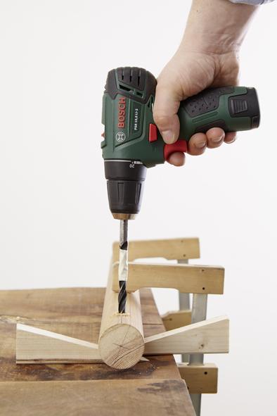 ÉTAPE 2 Dans un deuxième temps, il s'agit de percer. Fixer pour cela le bâton de bois sur la table de travail de sorte que la ligne de repère de gauche soit précisément orientée vers le haut. Afin que les baguettes soient ensuite solidement fixées dans le bâton malgré leur forme étroite, mesurer avant le perçage à l'aide du mètre ruban la circonférence de la tête des baguettes (pointe en forme de boule) et calculer le diamètre (voir encadré). Dans cet exemple, il fait 10 mm. Déterminer ensuite la hauteur du manche de la baguette qui a un diamètre de 10 mm exactement comme la tête. Pour assurer une stabilité optimale, les baguettes devraient ensuite être enfoncées dans le bâton jusqu'à cette hauteur déterminée. Astuce : marquer la profondeur nécessaire des trous avec un peu de ruban crêpe sur la mèche à bois. Cela signifie que les trous doivent être percés avec la profondeur correspondante. Pour cela, mesurer à l'aide du mètre ruban la longueur de manche comprise entre le point déterminé et la tête de la baguette. Il est indispensable de veiller à ce que le bâton ne soit pas transpercé. Ensuite, percer les trous marqués au préalable avec la profondeur nécessaire dans le bâton de bois à l'aide de la perceuse-visseuse sans fil PSR 10,8 LI-2 Bosch et d'une mèche à bois (10 mm). Enfin, fixer le bâton à la table de travail de sorte que la ligne de repère de droite soit orientée vers le haut et pour faire les trous de ce côté. Le diamètre peut être calculé à l'aide de .la circonférence grâce à la formule suivante : circonférence / PI (env. 3,142) = diamètre.